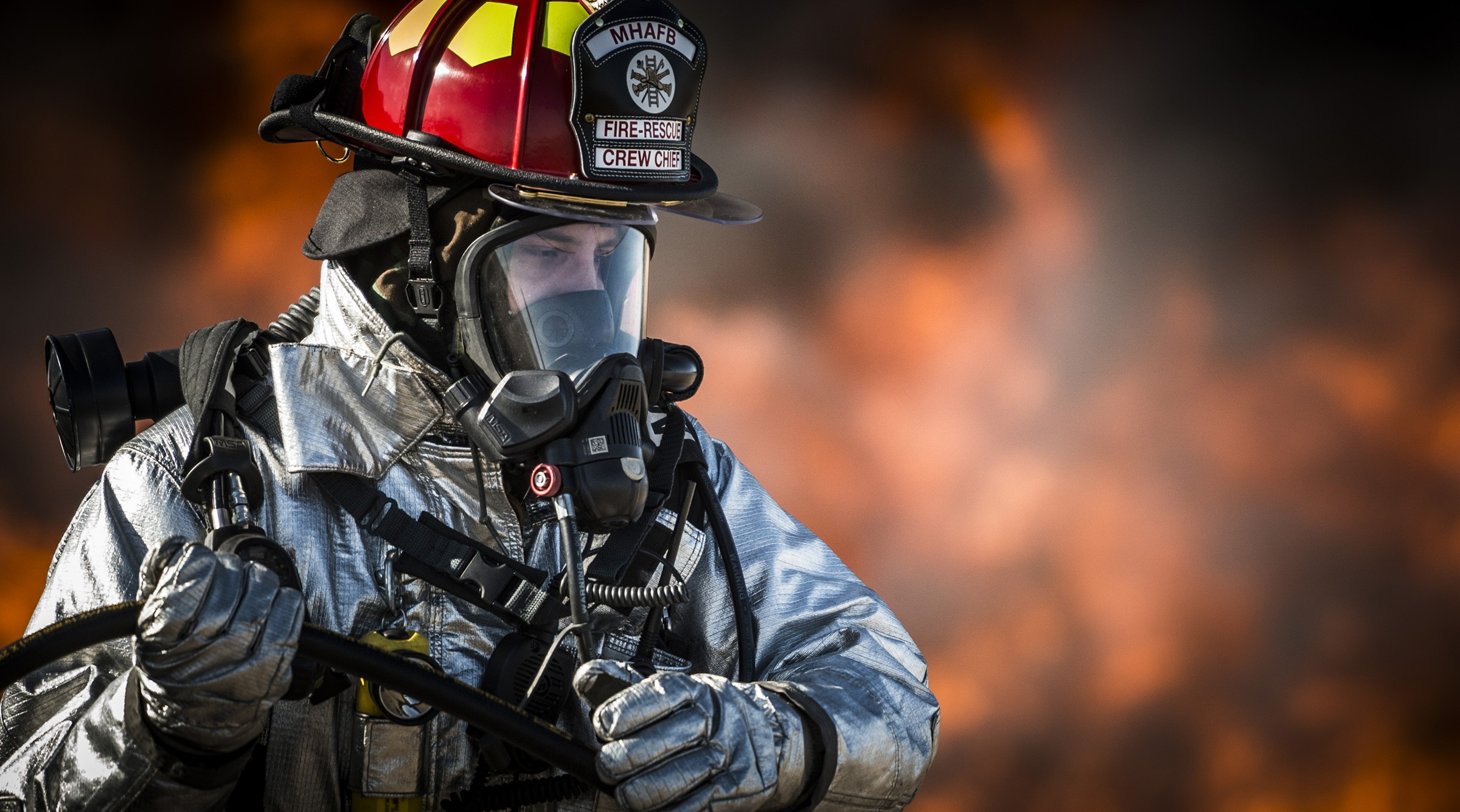 Firefighter with full personal protection gear standing in front of a fire